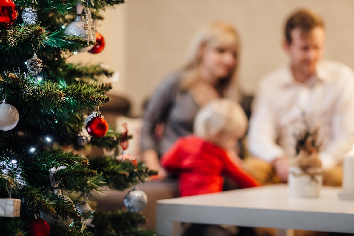 two parents coparenting during the holidays with a christmas tree and child